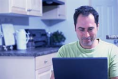 A man using a laptop computer in his kitchen